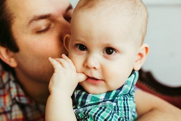 Le garçon mord le doigt tandis que le père l'embrasse