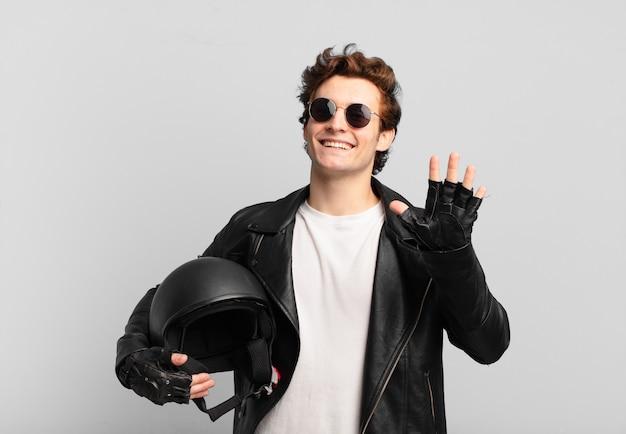 Garçon de motard souriant joyeusement et joyeusement, agitant la main, vous accueillant et vous saluant, ou disant au revoir