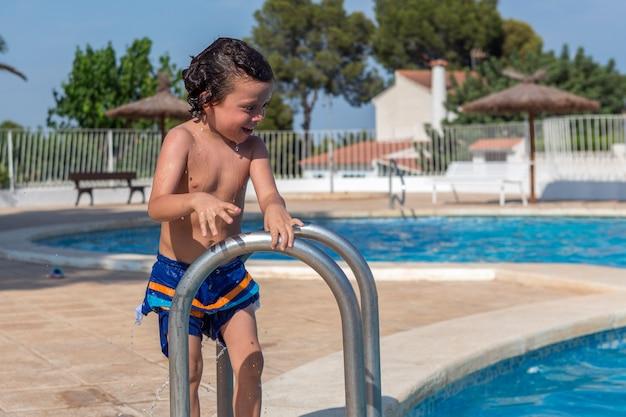 Le garçon mouillé juste hors de la piscine regarde dans l'eau et sourit avec amusement