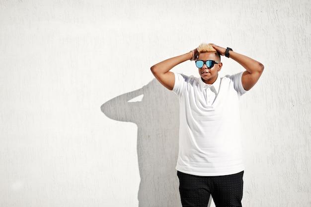 Garçon musulman arabe élégant avec à l'origine des cheveux et des lunettes de soleil posés dans les rues au toit contre le mur blanc.