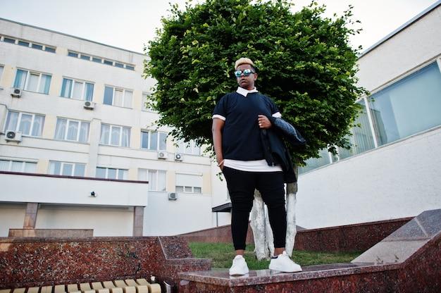 Garçon musulman arabe élégant avec à l'origine des cheveux et des lunettes de soleil posés dans les rues