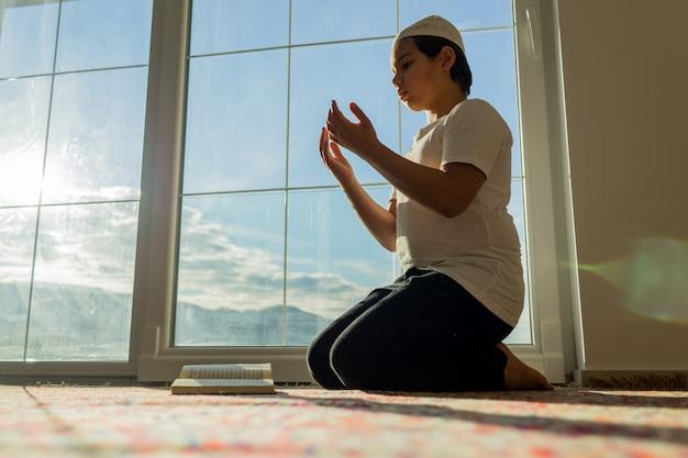 Garçon musulman priant pour dieu avec ses mains