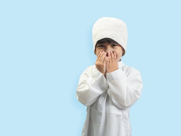 Un garçon musulman vêtu d'une robe à la recherche de bénédictions à dieu