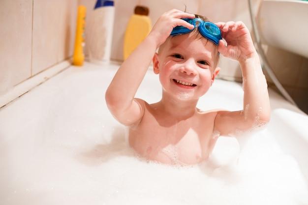 Un garçon nage dans la baignoire