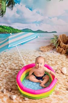 Garçon nageant dans une piscine gonflable sous un parasol sur une plage de sable avec des palmiers au bord de la mer