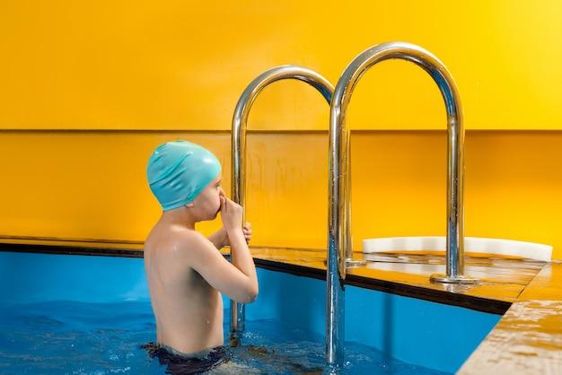 Garçon nageant dans la piscine intérieure s'amusant pendant les cours de natation