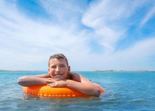 Garçon nager dans le lac à la journée ensoleillée d'été, il flotte avec un anneau flottant orange et sourit