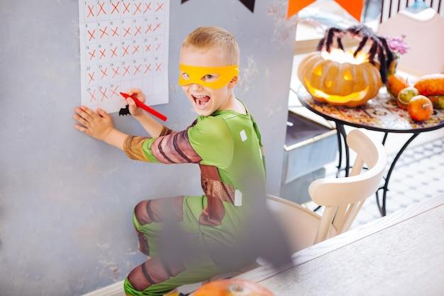 Garçon ninja. garçon aux cheveux blonds vêtu d'un costume d'halloween de tortue ninja se sentant extrêmement fou et diverti