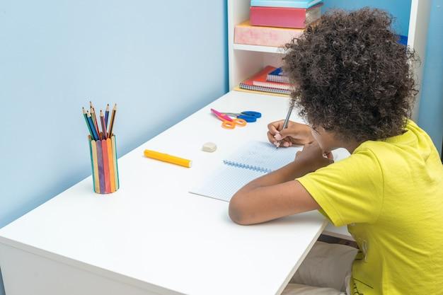Garçon noir assis au bureau et faisant ses devoirs.