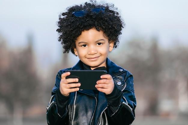 Garçon noir aux cheveux afro et veste en cuir, à l'aide de son smartphone, souriant. dans un fond de parc. image avec copyspace. concept d'enfants, de téléphones intelligents et de personnes noires