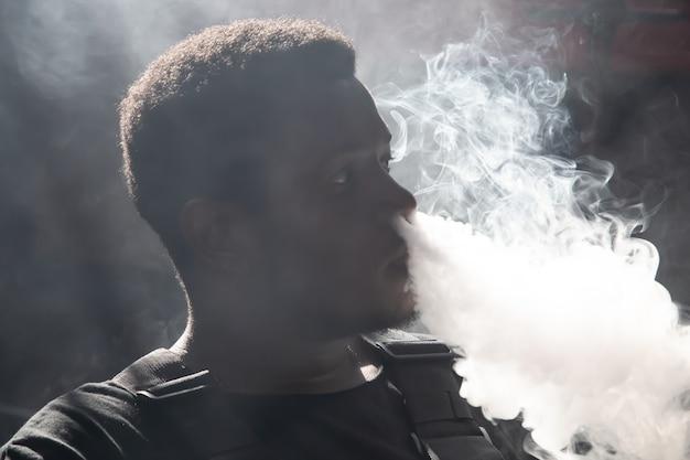 Garçon noir, fumer, depuis, a, vapper, et, souffler, les, fumée, depuis, les, nez
