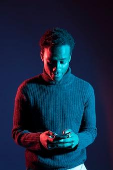 Garçon noir posant avec une lumière bleue