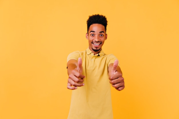 Garçon noir raffiné montrant les pouces vers le haut avec un sourire surpris. photo intérieure d'un homme africain de bonne humeur avec une coiffure drôle.