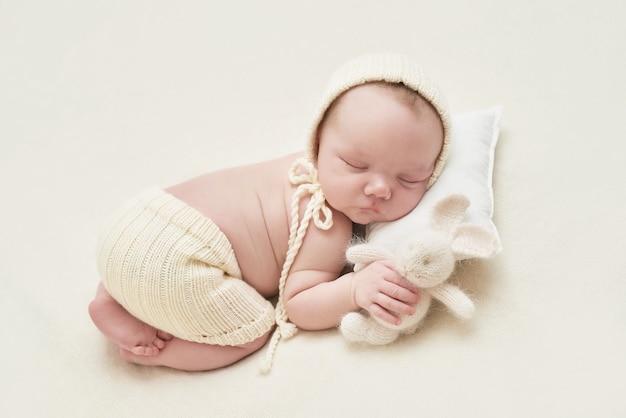 Garçon nouveau-né dormant sur fond blanc. concept de médecine et de santé, maternité et paternité heureuses. enfant au chapeau et avec lapin. carte de pâques. maternité et clinique. fête des pères et mères