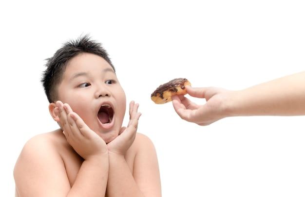 Garçon obèse mange beignet de la main de la mère isolée