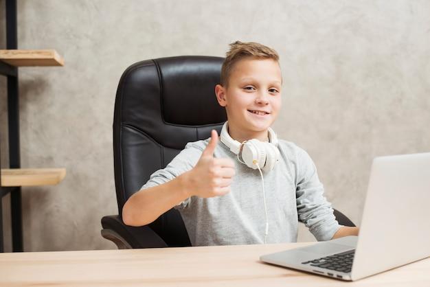 Garçon avec ordinateur portable au bureau