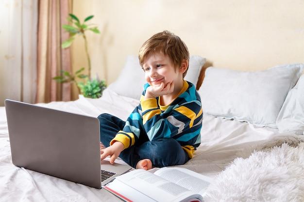 Garçon avec ordinateur portable au lit