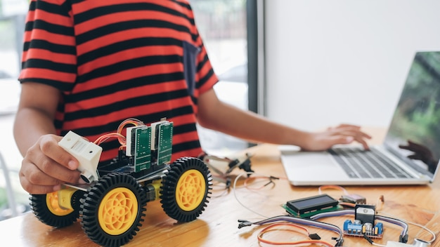 Garçon avec ordinateur tablette programmant des jouets électriques et des robots de construction.