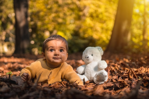 Garçon avec un ours en peluche blanc dans le parc sur un coucher de soleil d'automne. éclairage naturel, bébé en milieu d'année allongé sur les feuilles des arbres