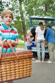 Garçon avec panier pique-nique tandis que la famille en arrière-plan au coffre de la voiture