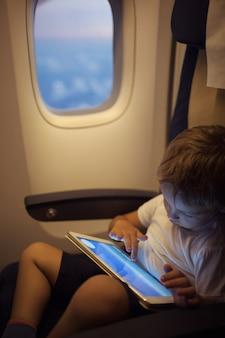 Garçon passant du temps avec une tablette pc pendant le vol