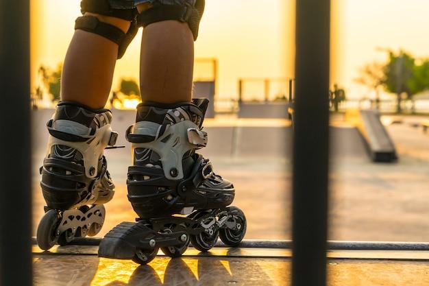 Le garçon de patin à roues alignées dans un parc public avec des équipements de protection sur le fond de coucher de soleil