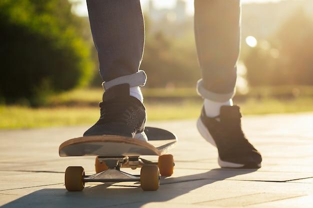 Garçon patineur dans un parc d'été. jambes pieds de l'homme en jeans à la mode et baskets élégantes sur un longboard skateboard asphalte . concept de skateboard pour les jeunes.