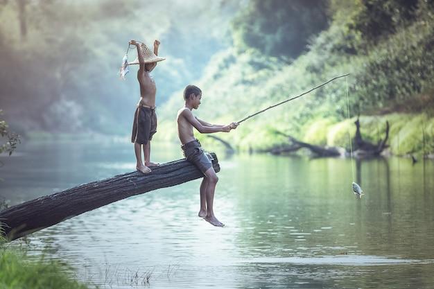 Garçon pêchant à la rivière