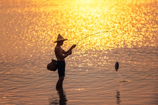 Garçon pêche au coucher du soleil sur le lac