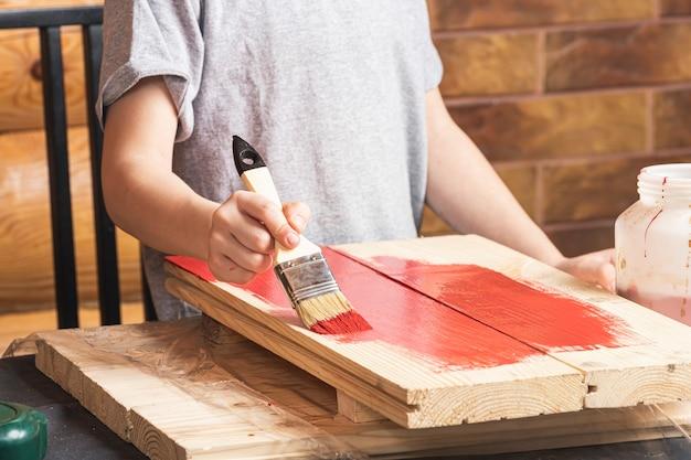 Un garçon peint un faux en bois avec un pinceau en rouge dans une maison de campagne