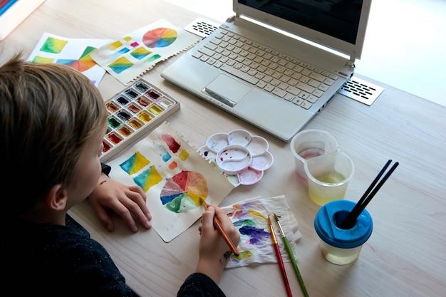 Garçon peinture des images avec des peintures à l'aquarelle pendant la leçon d'art