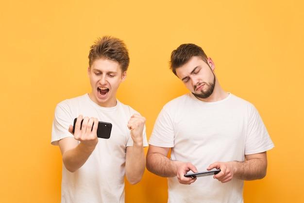 Garçon perdant et garçon gagnant jouant ensemble et participant à des jeux vidéo sur smartphones isolés jaune.