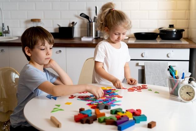 Garçon et petite fille à la maison dans la cuisine, s'asseoir à une table ronde blanche et jouer à des jeux de société