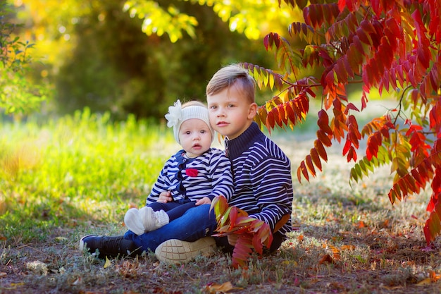 Le garçon avec la petite soeur assis sous un arbre dans le parc