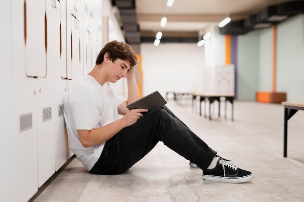 Garçon plein coup lisant sur le sol à l'école