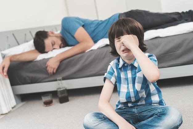 Le garçon pleure pendant que son père dort ivre sur le lit