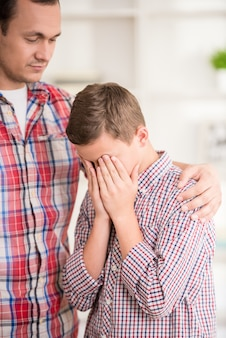 Un garçon pleure tandis que son père le gronde.