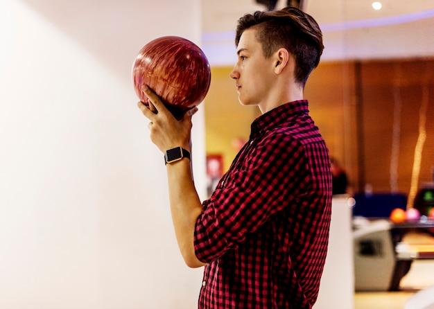 Garçon sur le point de lancer un concept de passe-temps et de loisirs de boule de bowling