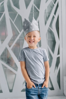 Garçon portant une couronne, un garçon qui rit comme un prince, un concept de développement pour rester à la maison.