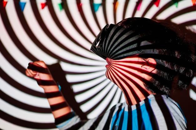 Garçon portant des lunettes de réalité augmentée sur un arrière-plan projeté en spirale
