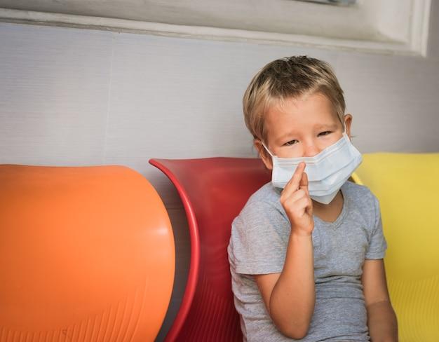 Garçon portant un masque facial jetable pour éviter une infection virale. protection antivirus