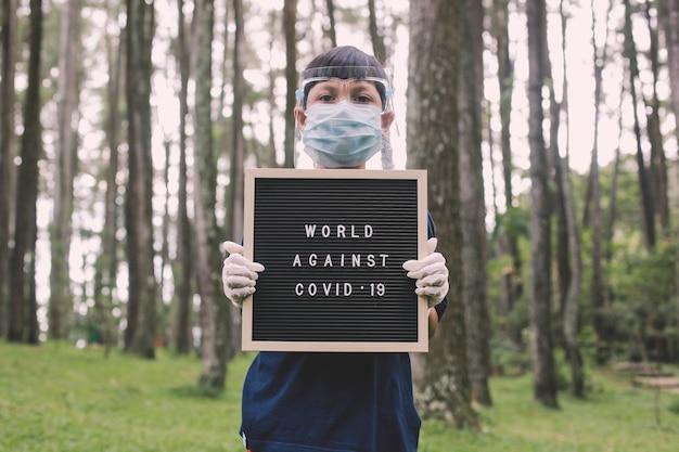 Garçon portant des masques faciaux et des gants en caoutchouc debout tout en maintenant le panneau aux lettres dit world against covid