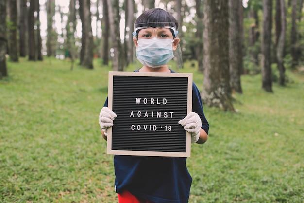 Garçon portant des masques et des gants en caoutchouc debout et tenant le panneau de lettres qui a écrit world against covid