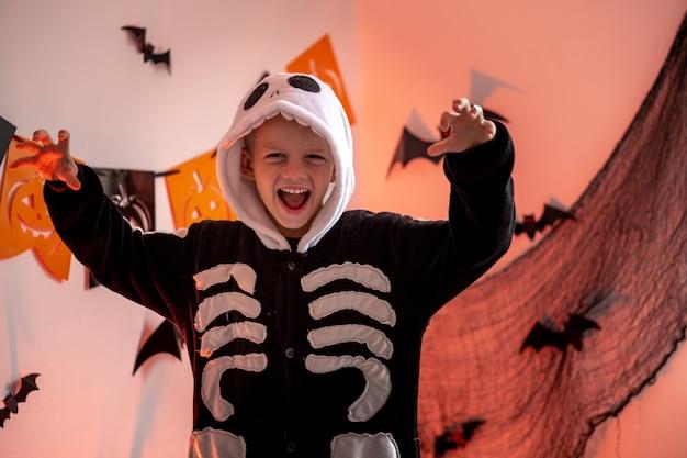 Garçon de portrait d'enfants d'halloween en costume de squelette d'halloween à la maison, le garçon est prêt pour le tour ou