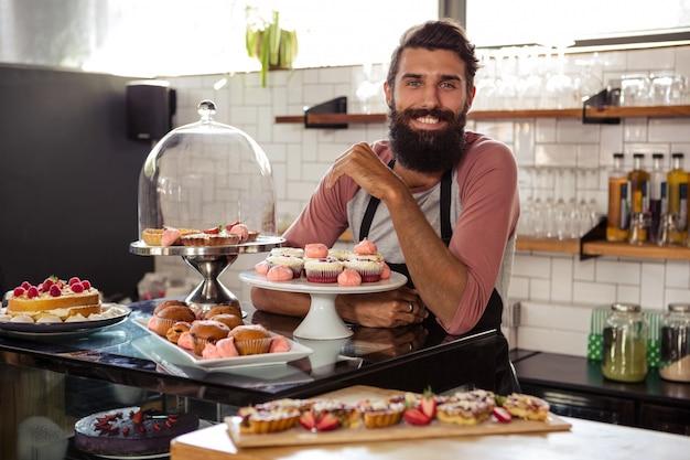 Garçon posant avec des gâteaux