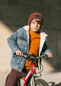 Garçon posant avec son vélo à l'extérieur dans la ville