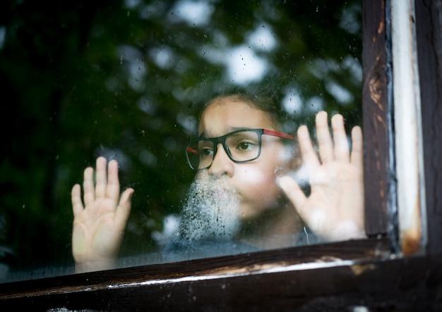 Un garçon pose sa main sur une fenêtre et regarde dehors