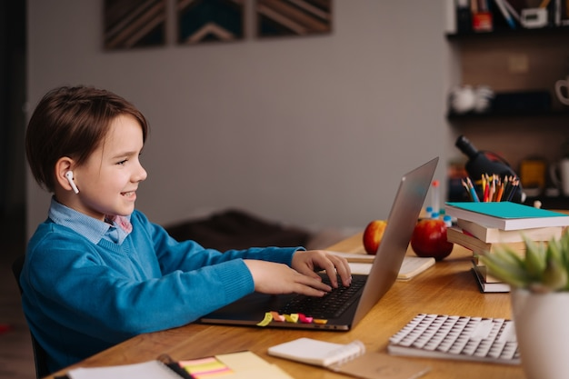 Un garçon préadolescent utilise un ordinateur portable pour faire des cours en ligne
