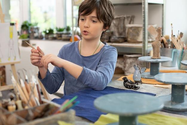 Garçon prenant peu de pinceau tout en sculptant des figures d'argile