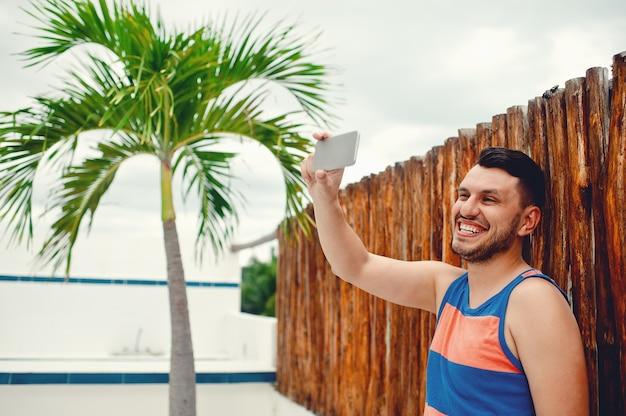 Garçon prenant un selfie avec un smartphone alors qu'il se tient devant un bois